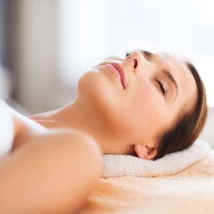 beauty and spa concept - beautiful woman in spa salon lying on the massage desk